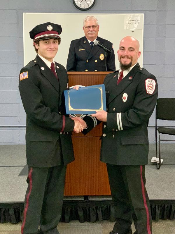 Firefighter Jack Lawton (L) is presented his certification by Assistant Chief Mike Esterlis (R)