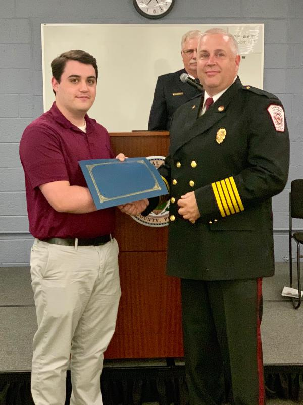 Firefighter Chris Rhodes (L) is presented his certification by Battalion Chief Mike Chapman (R)