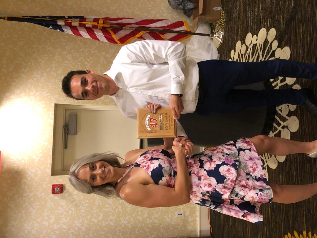 """Membership Secretary Jack Jacobson (R) presents Mackenzie Holmes (L) a 10 Years Of Continuous Service Award, which she is accepting on behalf of her brother Michael """"Pike"""" Holmes."""